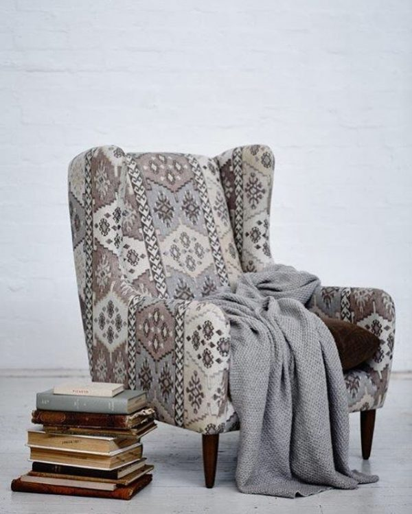 reading chair in with grey throw and books beside brightly patterend